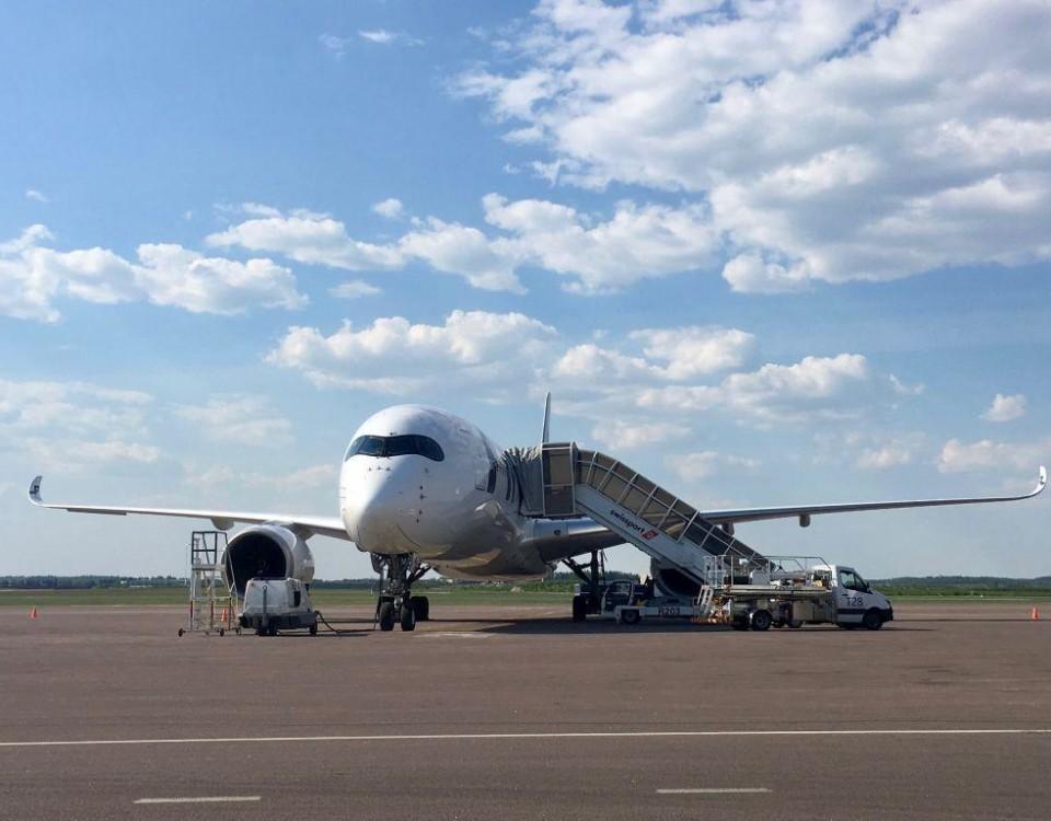ett flygplan står på ett öppet asfalterat område.