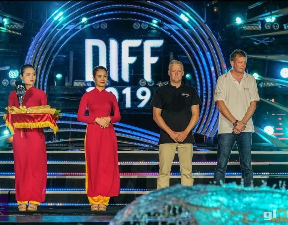 Två asiatiska kvinnor med röda klänningar står bredvid två medlemmar i vinnargruppen
