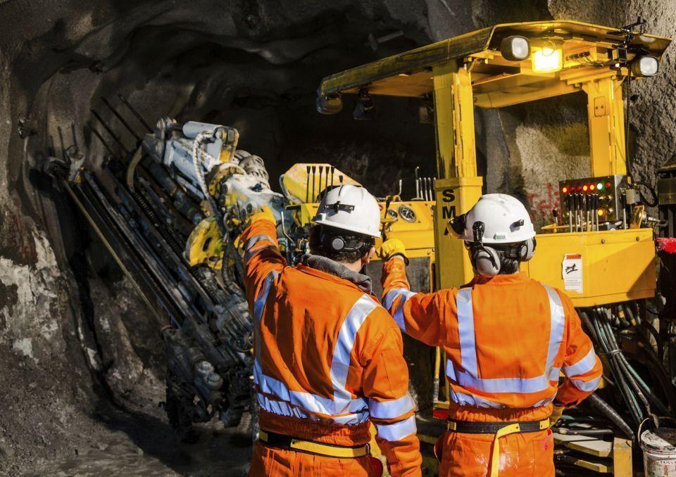 två personer klädda i orange skyddsutrustning inne i en gruva tillsammans med ett stort gult arbetsfordon.