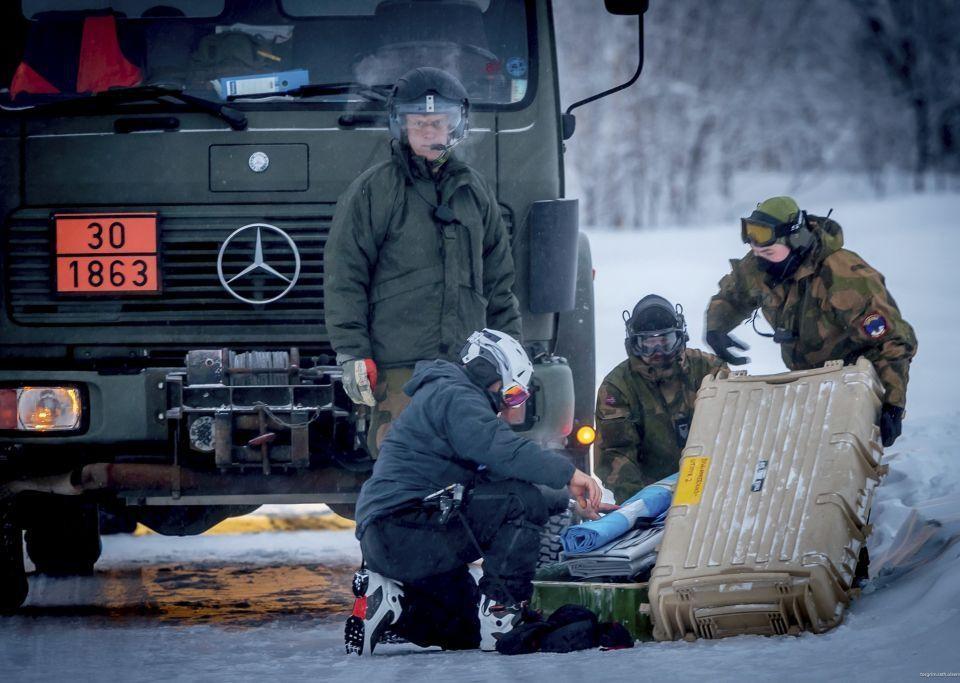 Fyra personer klädda i varma kläder samlas kring någon form av utrustning. I bakgrunden syns en lastbil.