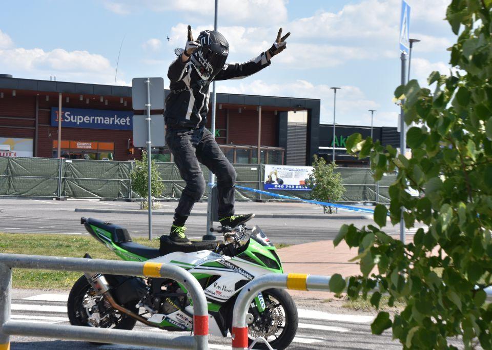 En man står på en motorcykel och visar segertecknet med sina händer.