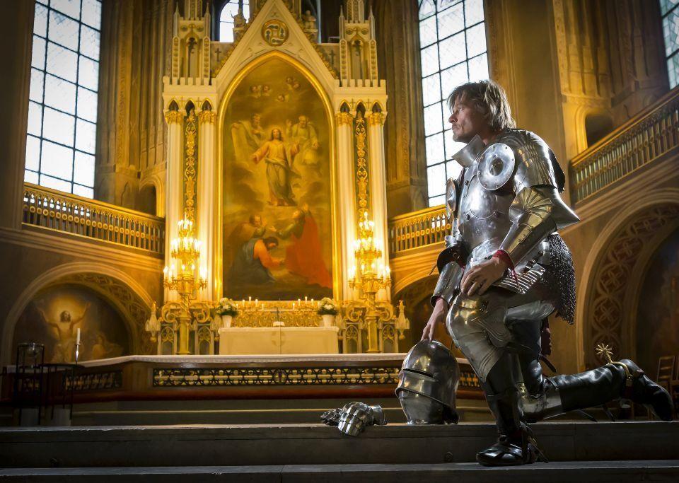 En person klädd i medeltida riddarkläder står knäböjd framför altaret i Åbo domkyrka.