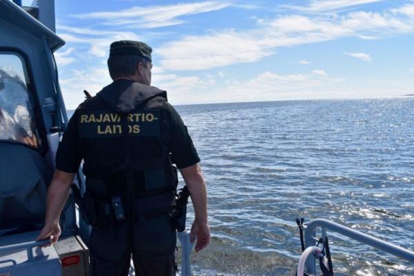 """En sjöbevakare står på en båt och tittar ut över havet. På hans rygg står det """"Rajavartiolaitos"""""""