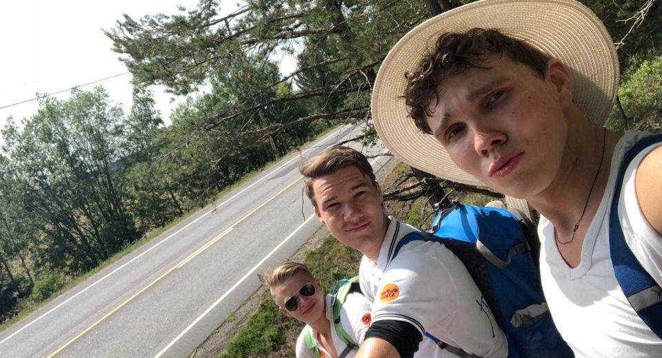 tre unga män vid en landsväg. Bilden är tagen som en selfie.