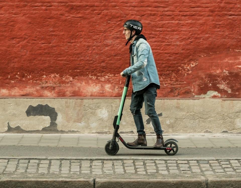 En person åker på en turkos elsparkcykel.