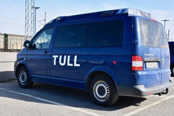 """En blå bil med texten """"Tull"""" skriven på sidan står parkerad."""