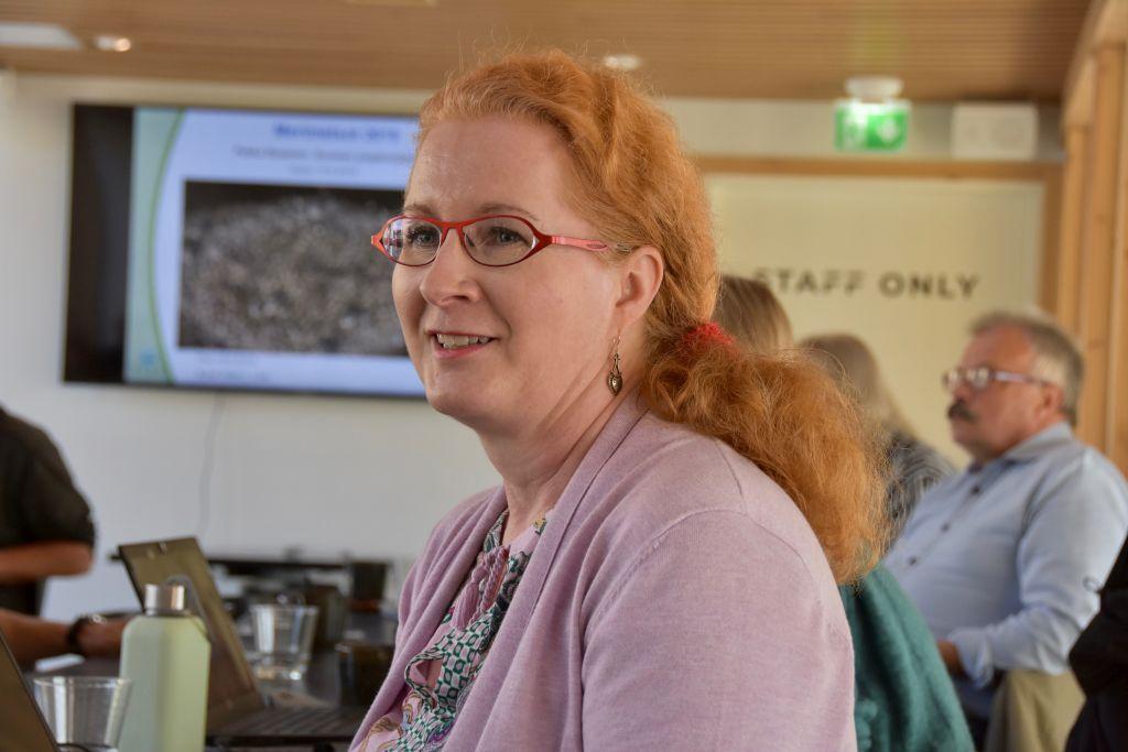 En kvinna står i ett konferensrum, i bakgrunden syns andra människor och på väggen projiceras en presentation.