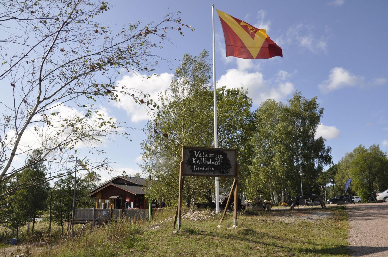 naturfint landskap med en byaflagga och en skylt: Välkommen till Kalkholmen. Foto: Emilia Örnmark.