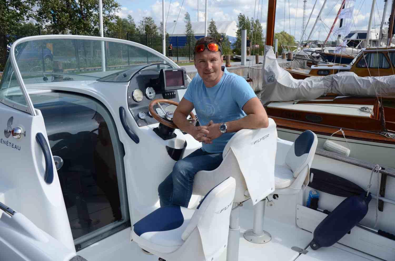 Man i t-skjorta ombord på en motorbåt.