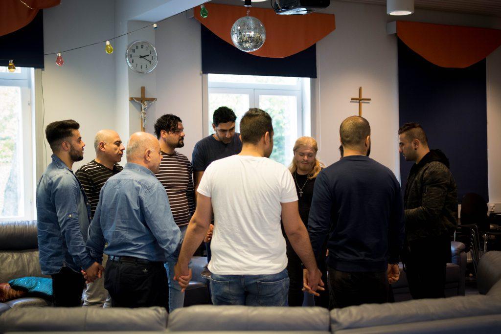 Män står i en ring och håller varandra i handen. Det hänger kors på väggen bakom.