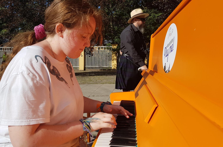 Flicka spelar piano utomhus