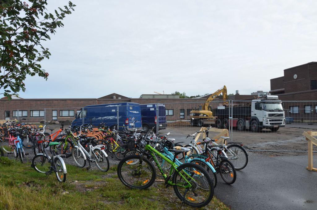 Cyklar står parkerade framför ett staket som omringar en byggarbetsplats