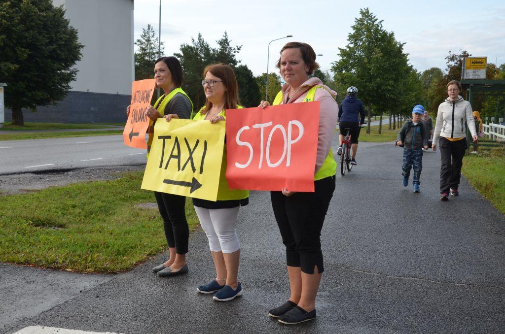 """Tre kvinnor står och håller i färggranna skyltar med texterna """"taxi"""" och """"stop""""."""