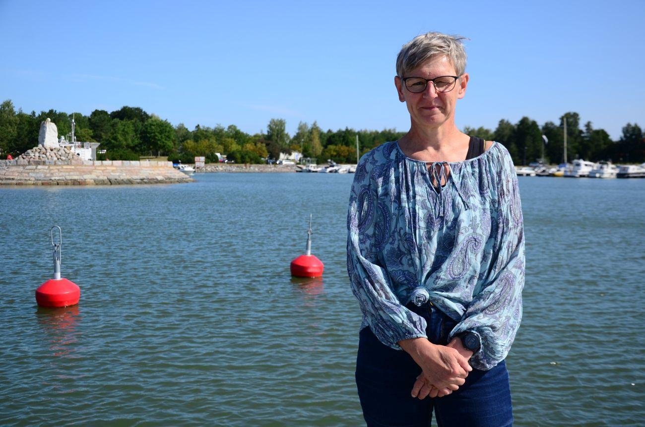 Kvinna står vid en strand, hav och bojar bakom henne