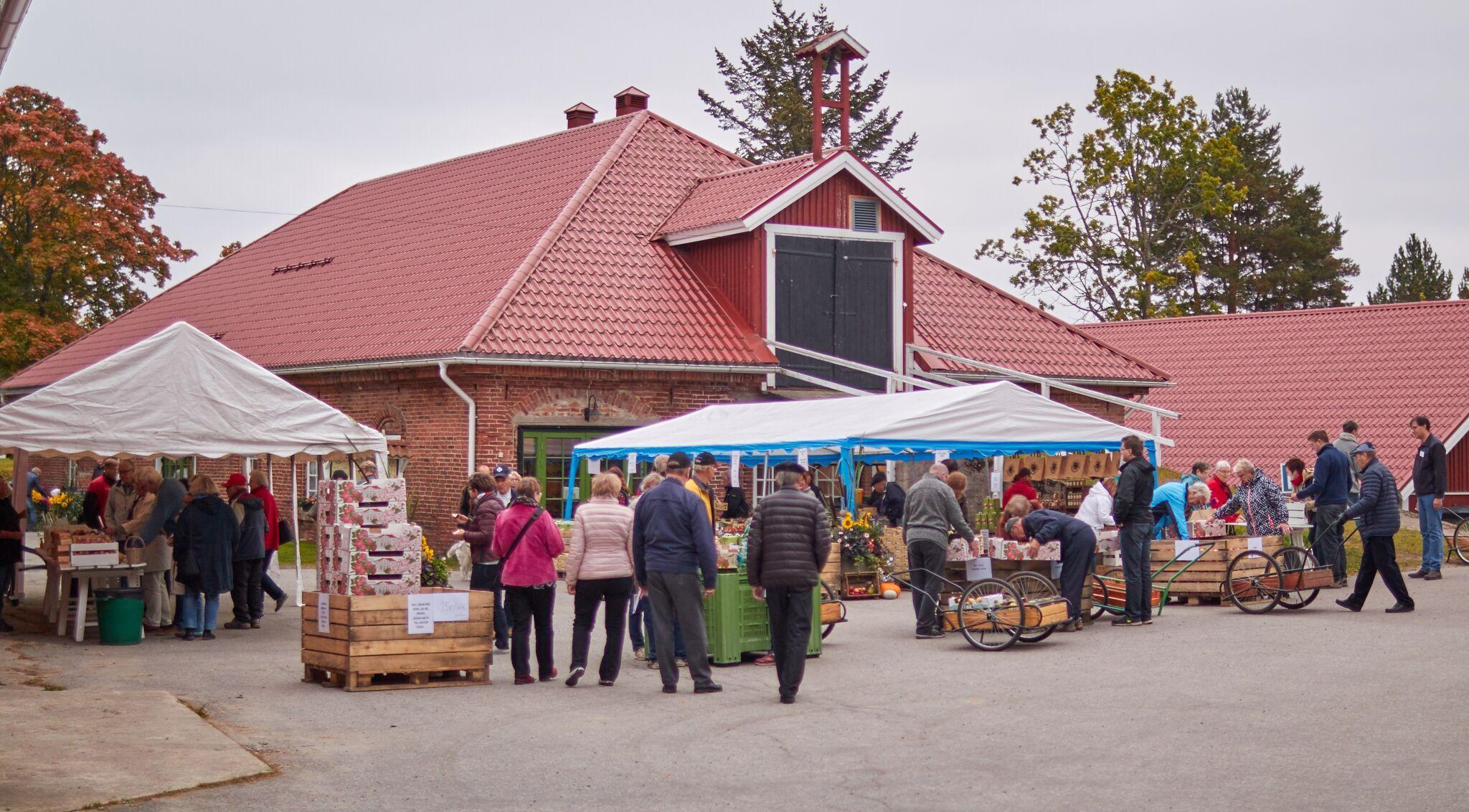 Marknadsstånd framför en byggnad. Mycket folk rör sig.