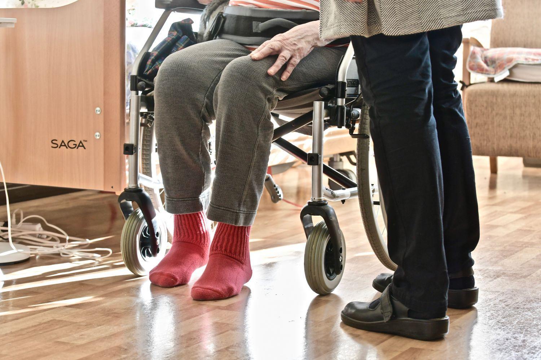 En äldre person som sitter på en rollator och enannan äldre person som står bredvid.