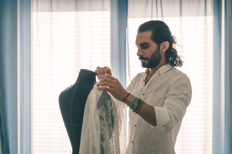 Bahaulddin Rawi iklädd vit skjorta, står vid fönstret i motljus och syr på en kreation som är upphängd på en skräddardocka.