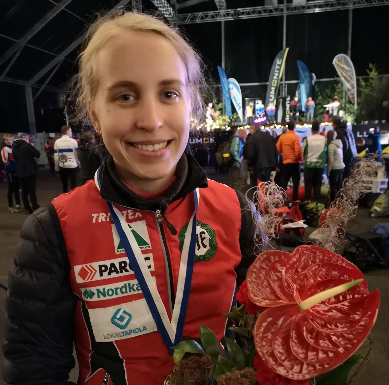 Amy Nymalm ler mot kameran med medalj kring halsen och en blombukett i handen.
