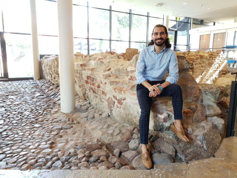 Bahaulddin Rawi sitter på ruinerna inne i Aboa Vetus café och ler mot kameran. Han är iklädd blå skjorta och mörka, rutiga byxor.