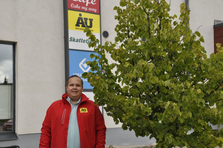 Man står i röd ÅU-rock vid en ÅU-skylt.
