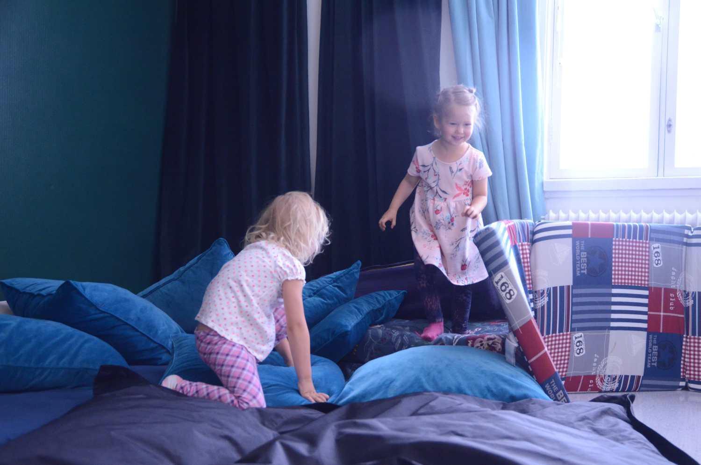 Två flickor hoppar på kuddar.