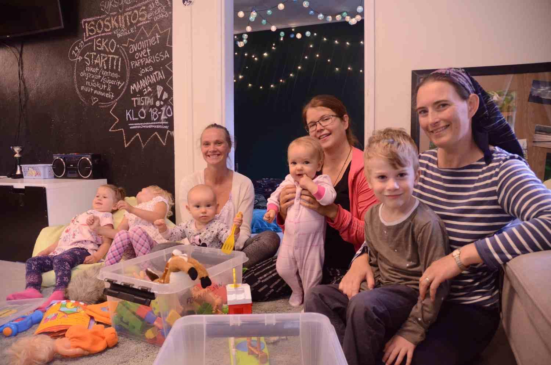 Barn och mammor sitter i ett rum med leksaker.