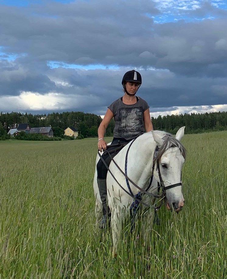 Dam sitter på en vit häst på en åker
