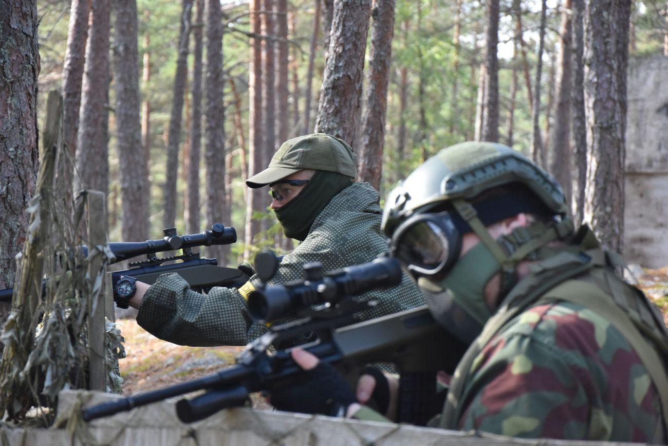 Två män iklädda stridsutrustning och med airsoftvapen spanar efter motståndare.