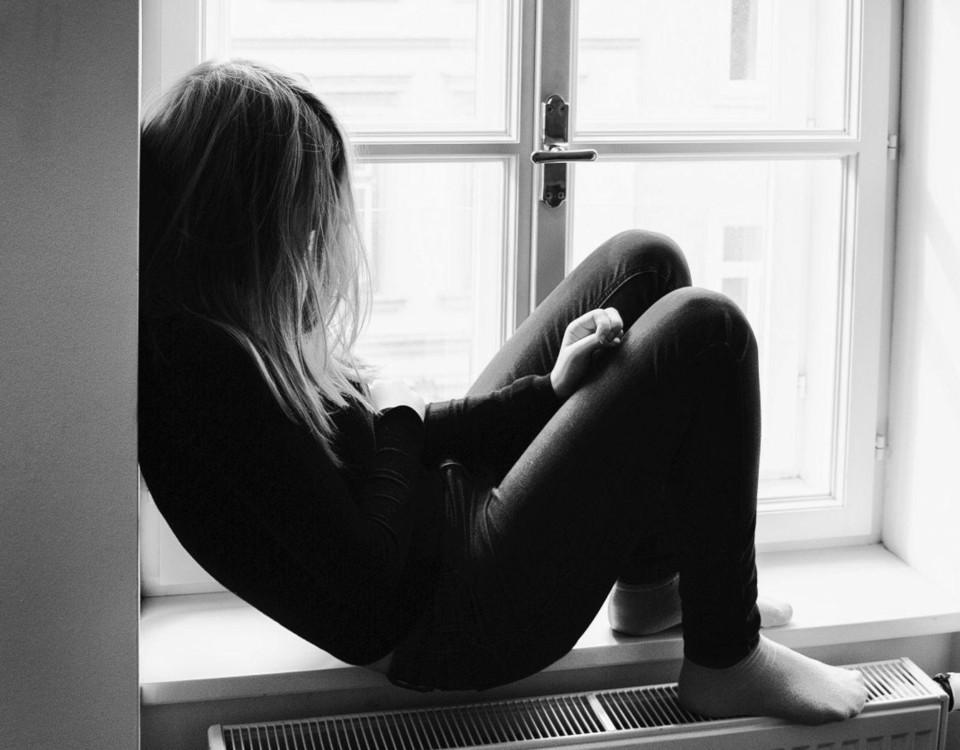 En flicka som sitter i en fönstersmyg.