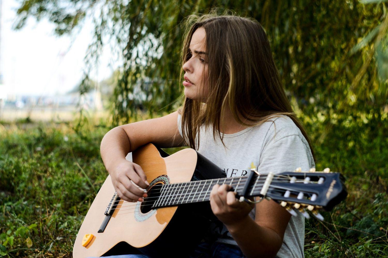 Flicka sitter på gräsmatta och spelar gitarr
