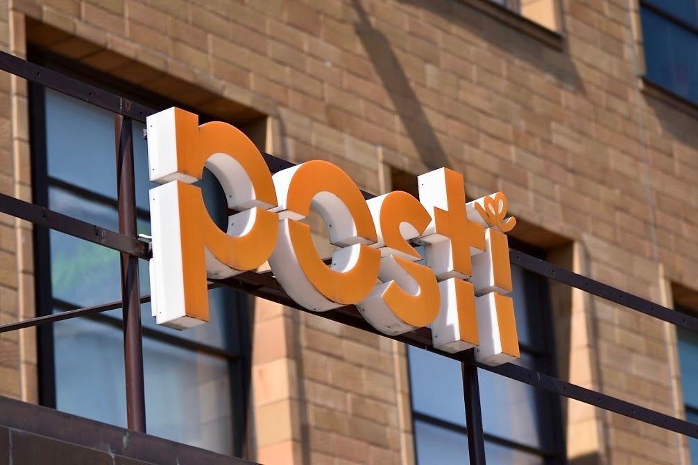 Posti med stora bokstäver på en tegelvägg.