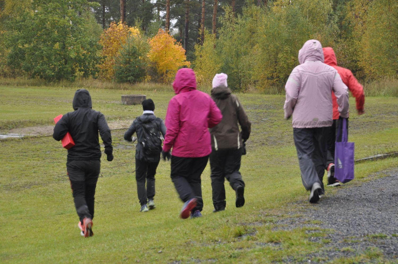 Sex damer i utekläder joggar iväg bort från kameran