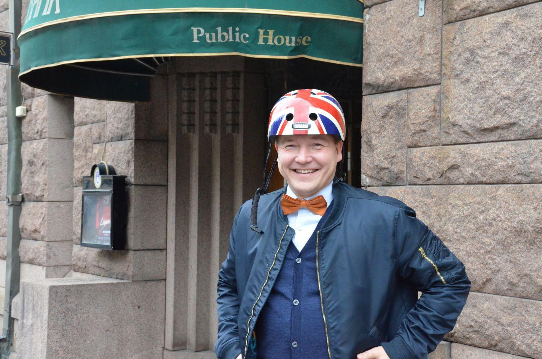 Leende man som står framför en krog. mannen bär en hjälm som pryds av den brittiska flaggan.n på.