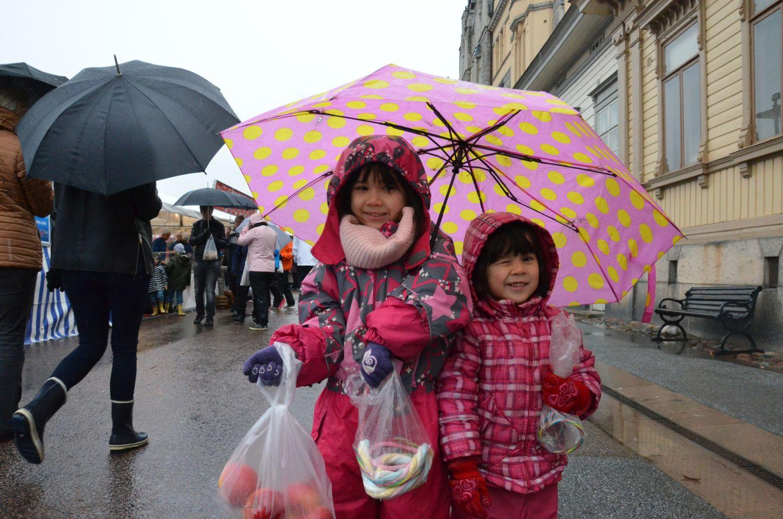 Två små flickor med paraplyer.