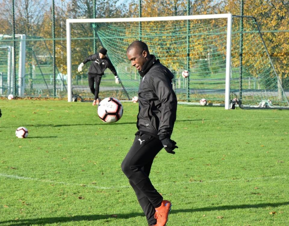 en fotbollsspelare trixar med bollen under ett träningspass