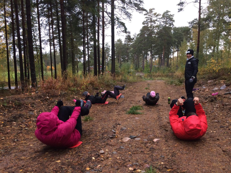Damer ligger på marken på en skogsväg och gör magmuskelövningar