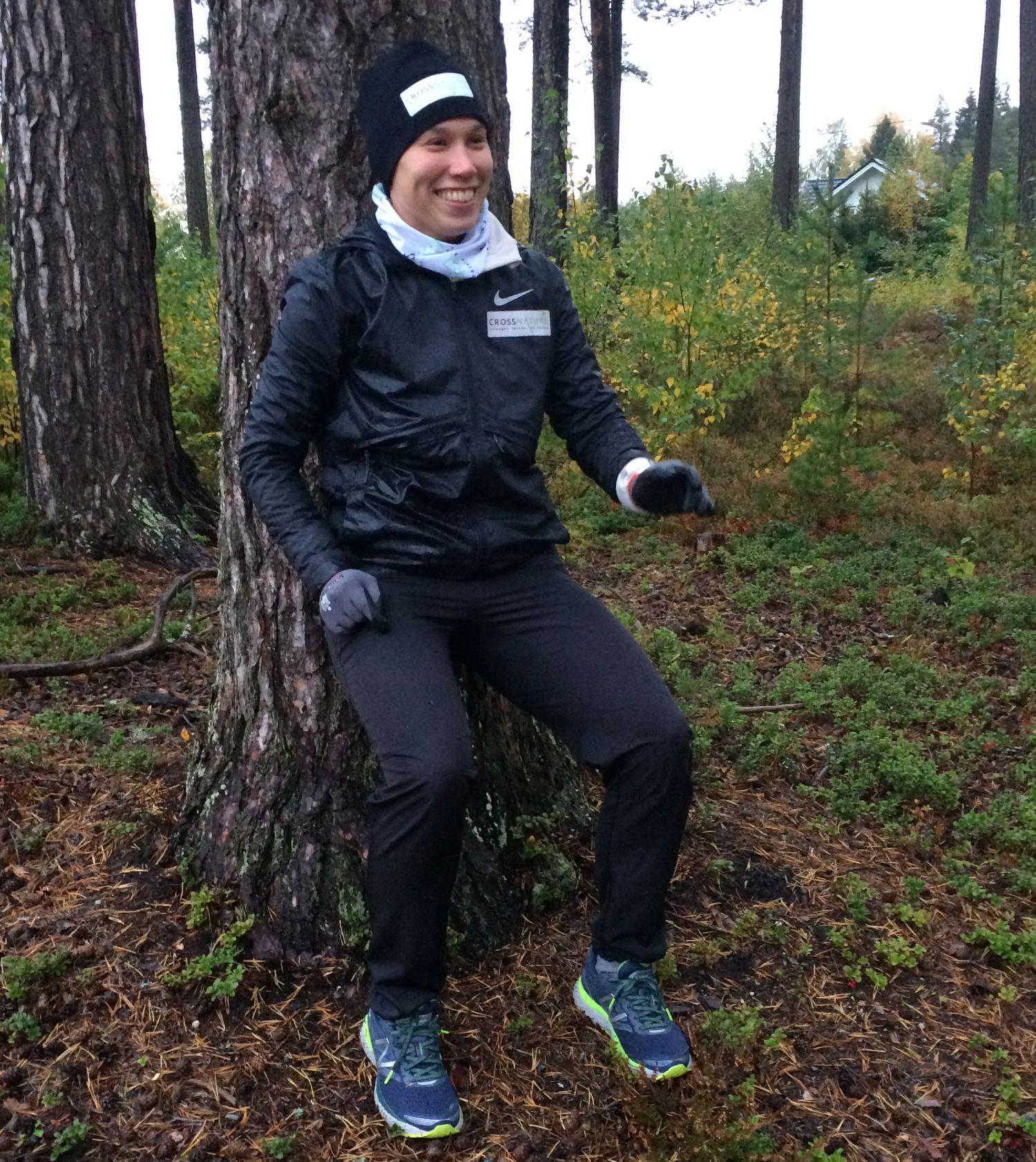 Dam i träningskläder sitter utan stol med ryggen mot ett träd