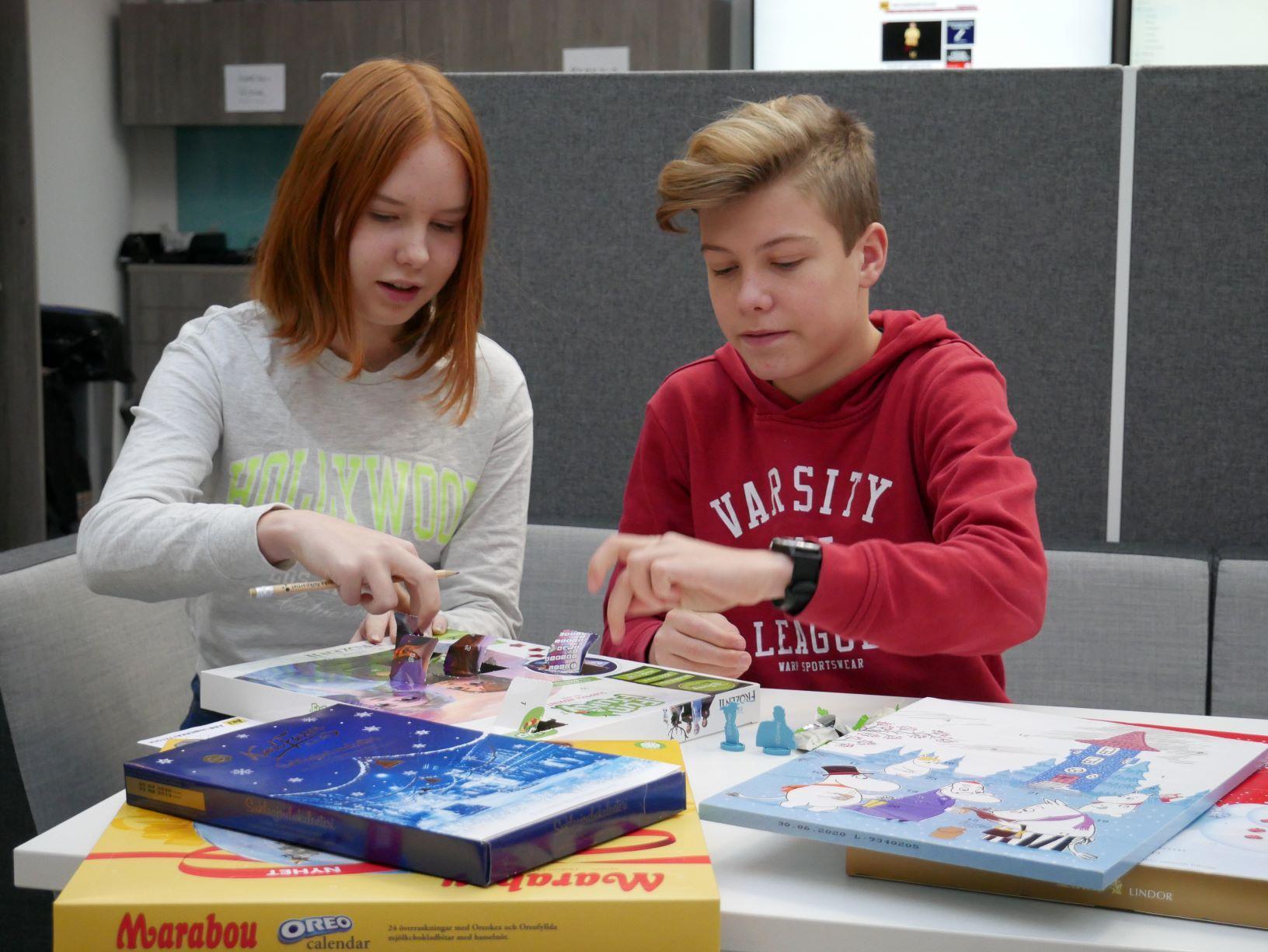 Två ungdomar provar chokladkalendrar