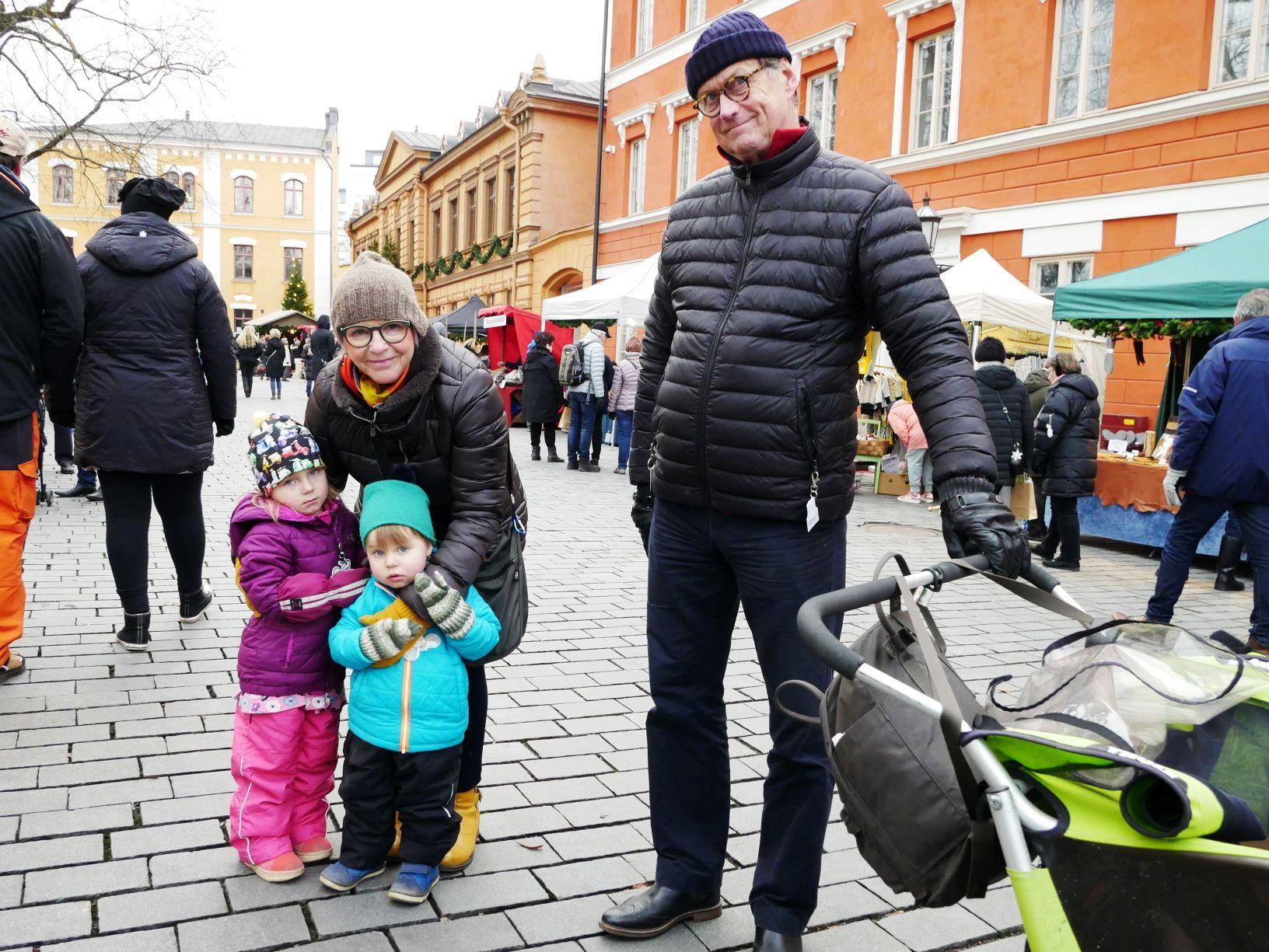 Två barn och två äldre personer på julmarknaden
