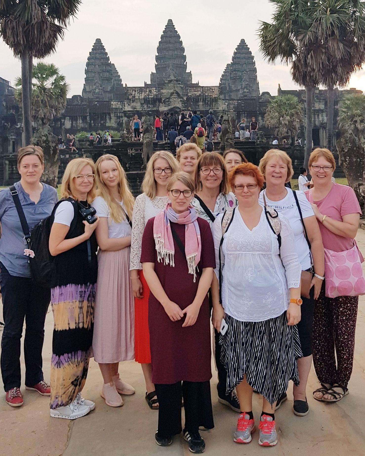 Grupp med kvinnor står framför ett tempel.