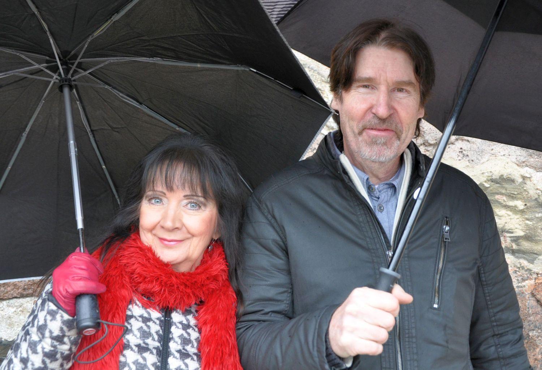 Kvinna och man med paraplyer