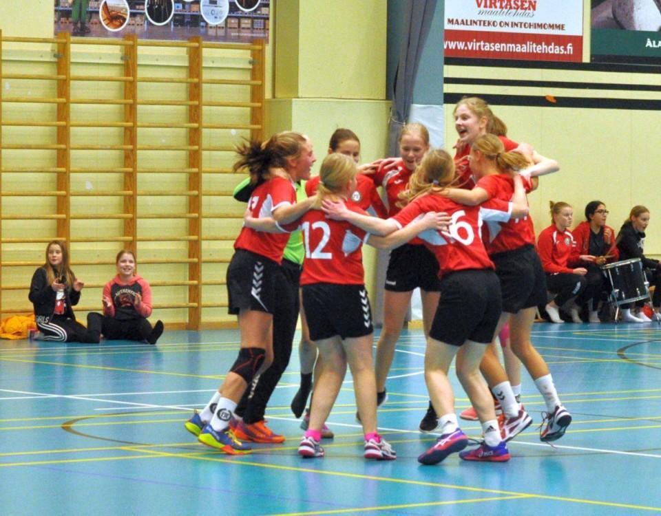 glada handbollsflickor i röda tröjor dansar