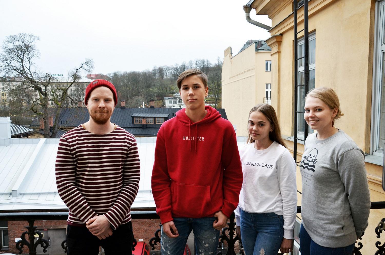 Fyra unga människor poserar utomhus.