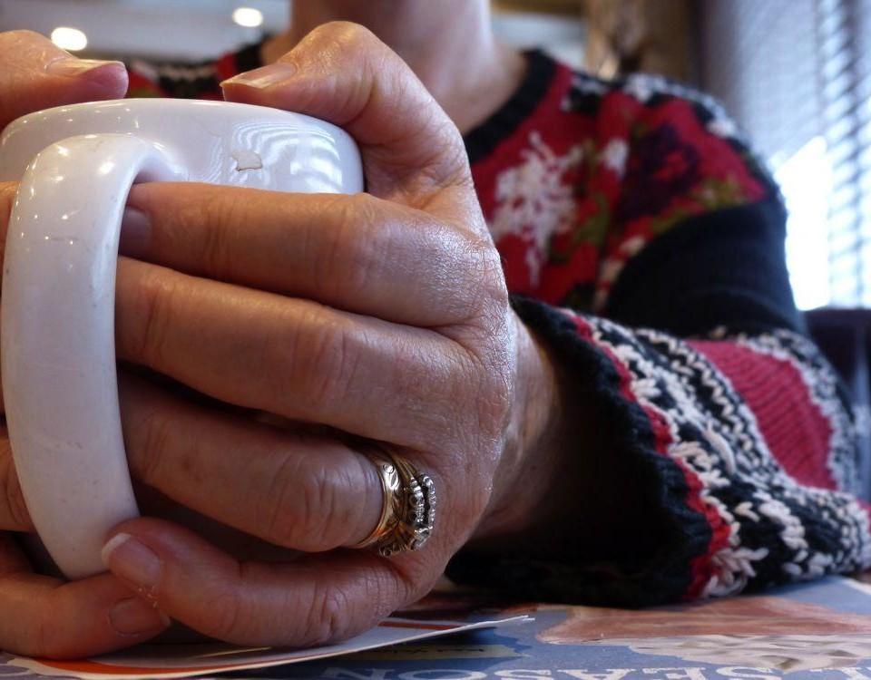 En hand som håller i en kopp.