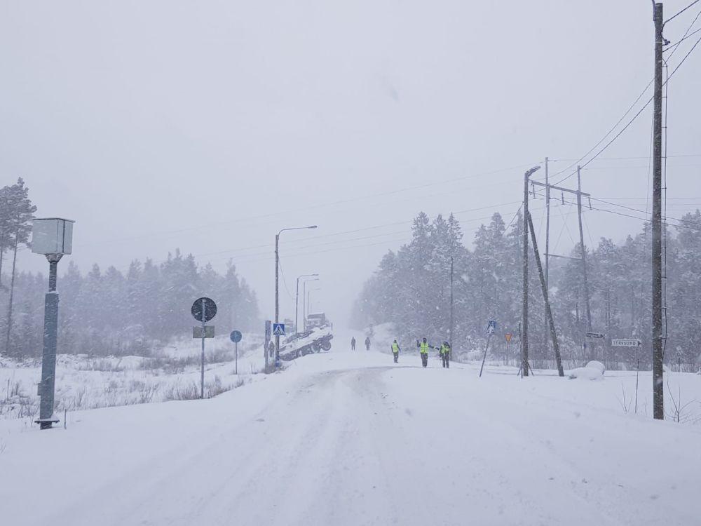 Snöig väg med ett stort fordon i diket.