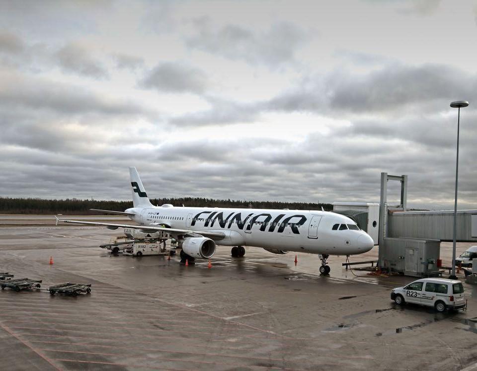 Ett Finnairflygplan står på ett flygfält i grått väder.