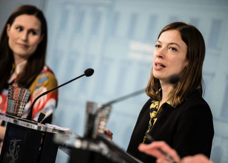 Två kvinnor står och talar i mikrofoner på en presskonferens.