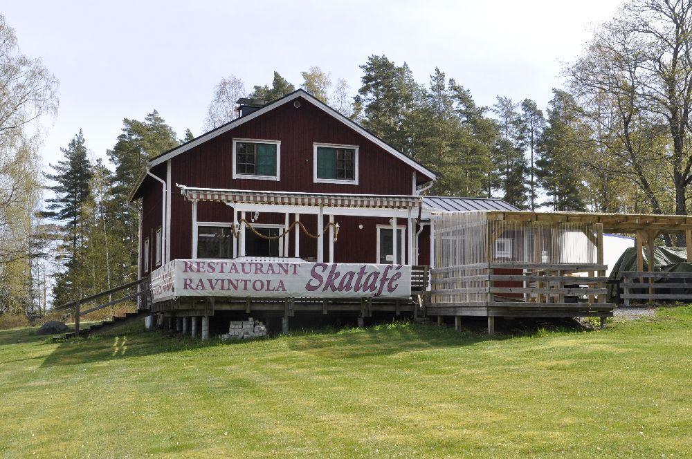 Röd restaurangbyggnad i trä på en gräsmatta. Stor terrass framför