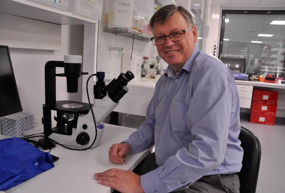 en man bakom ett mikroskop