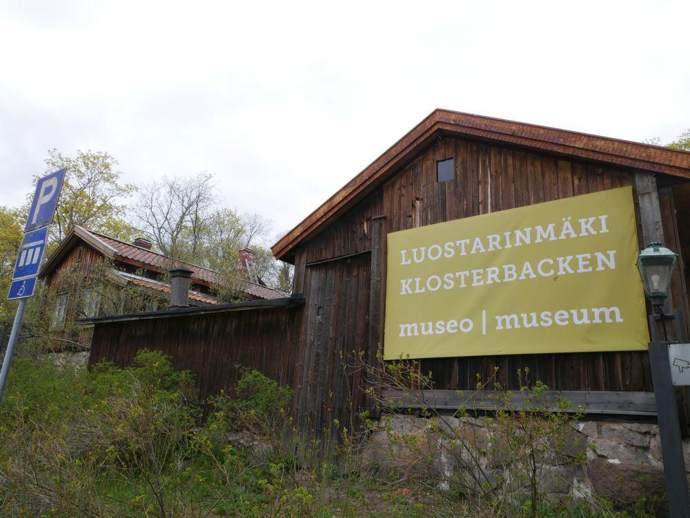 """Ett gammalt trähus med en stor grön reklamskylt med texten """"Luostarimäki, Klosterbacken"""""""